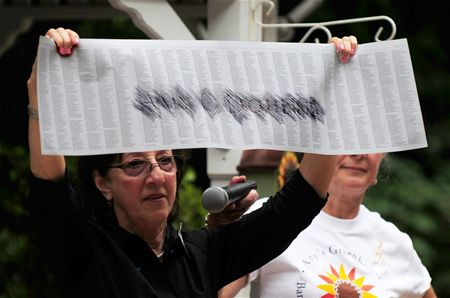 Geraldine Davie, Amy's mother, holds up etching of daughter's engraved name from NYC monument