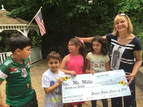 Children present check to Millie at Amy's Greenhouse
