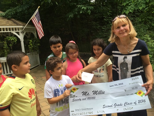 Millie Receives Check from second graders